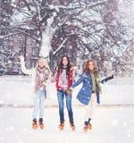 Muchacha joven y bonita que patina en hielo-pista al aire libre del aire abierto en los wi fotos de archivo libres de regalías