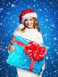 Muchacha joven y hermosa con el regalo de Navidad sobre vagos azules Foto de archivo