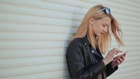 Muchacha joven y hermosa de moda con un smartphone en manos La muchacha está mirando la pantalla del teléfono Contra a almacen de video