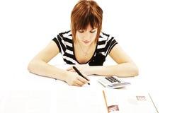 Muchacha joven y hermosa del estudiante en el escritorio fotografía de archivo libre de regalías
