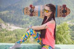 Muchacha joven y hermosa del hippie con el monopatín del longboard en la montaña Fotos de archivo