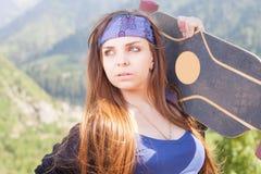 Muchacha joven y hermosa del hippie con el monopatín del longboard en la montaña Fotografía de archivo