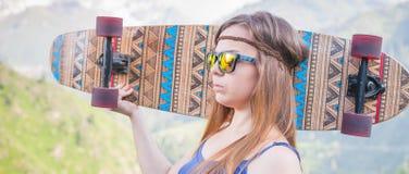 Muchacha joven y hermosa del hippie con el monopatín del longboard en la montaña Imagen de archivo