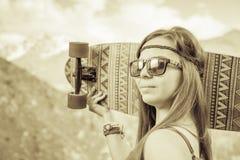 Muchacha joven y hermosa del hippie con el monopatín del longboard en la montaña Imágenes de archivo libres de regalías