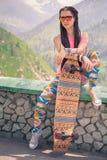 Muchacha joven y hermosa del inconformista con el monopatín del longboard en la montaña Foto de archivo