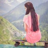 Muchacha joven y hermosa del inconformista con el monopatín del longboard en la montaña Imágenes de archivo libres de regalías