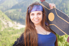 Muchacha joven y hermosa del inconformista feliz con el monopatín en la montaña Fotografía de archivo