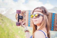 Muchacha joven y hermosa del inconformista feliz con el monopatín en la montaña Imagenes de archivo