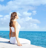 Muchacha joven y hermosa en la ropa de deportes blanca que hace yoga en un cortejar Fotos de archivo