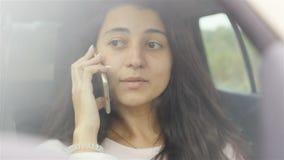 Muchacha joven y hermosa que habla en el teléfono en el coche Primer Cámara lenta almacen de metraje de vídeo