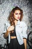 Muchacha joven y hermosa que presenta contra la pared con el graffit de plata Imagenes de archivo