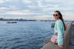 Muchacha joven y hermosa que se sienta en el terraplén del río ella mira la puesta del sol y envía el paso cerca St Petersburg, R Fotografía de archivo