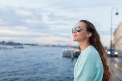Muchacha joven y hermosa que se sienta en el terraplén del río ella mira la puesta del sol y envía el paso cerca St Petersburg, R Imagenes de archivo