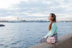 Muchacha joven y hermosa que se sienta en el terraplén del río ella mira la puesta del sol y envía el paso cerca St Petersburg, R Fotografía de archivo libre de regalías