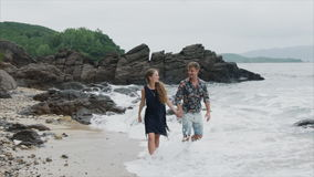 Muchacha joven y hombre de los pares que caminan a lo largo de la playa que habla y que lleva a cabo las manos, vista delantera H almacen de metraje de vídeo