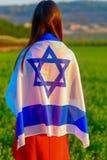 Muchacha jud?a con la bandera de Israel en paisaje que sorprende en verano hermoso foto de archivo