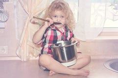Muchacha juguetona del niño con artículos de cocina y productos alimenticios en cocina Foto de archivo libre de regalías