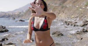 Muchacha juguetona en cara de la cubierta del bikini almacen de metraje de vídeo