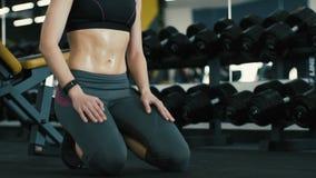 Muchacha juguetona en el fondo del gimnasio, ejercicios de respiración, cuerpo aceitoso almacen de metraje de vídeo