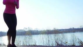 Muchacha juguetona que activa a lo largo de la orilla del río durante salida del sol o puesta del sol el concepto sano de la form almacen de video