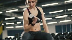Muchacha juguetona que hace ejercicios con las pesas de gimnasia, trabajando en gimnasio, almacen de video