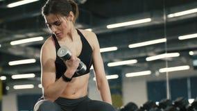 Muchacha juguetona que hace ejercicios con las pesas de gimnasia, trabajando en gimnasio, metrajes