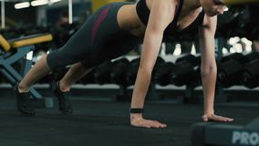 Muchacha juguetona que hace el tablón en el fondo del gimnasio metrajes