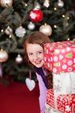 Muchacha juguetona que mira alrededor de los regalos apilados Imágenes de archivo libres de regalías