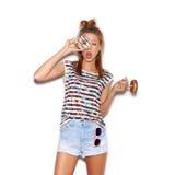 Muchacha juguetona que sostiene el buñuelo en su ojo Fotografía de archivo