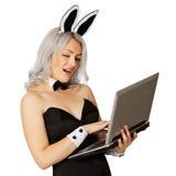 Muchacha juguetona vestida como conejo con una computadora portátil Fotos de archivo