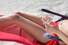 Muchacha la playa en silla de cubierta con un vidrio Fotos de archivo