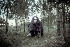 Muchacha larga del pelo con maquillaje asustadizo en el bosque Imagenes de archivo