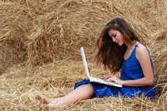 muchacha Largo-cabelluda que se sienta en el heno con la computadora portátil Foto de archivo libre de regalías