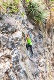 Muchacha latina adolescente que sube una pared vertical de la roca Imagen de archivo
