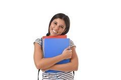 Muchacha latina de moda del estudiante que celebra la sonrisa de la mochila de la carpeta y del libro de la libreta que lleva fel Foto de archivo