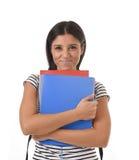 Muchacha latina de moda del estudiante que celebra la sonrisa de la mochila de la carpeta y del libro de la libreta que lleva fel Fotografía de archivo