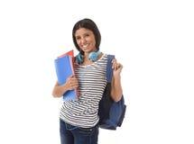 Muchacha latina de moda del estudiante que celebra la sonrisa de la mochila de la carpeta y del libro de la libreta que lleva fel Fotografía de archivo libre de regalías