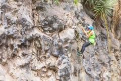 Muchacha latina del adolescente que sube una pared vertical de la roca Imagen de archivo libre de regalías