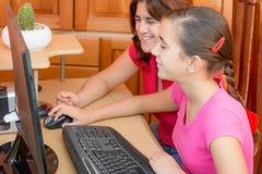 Muchacha latina feliz y su madre joven que trabajan en un ordenador Fotos de archivo