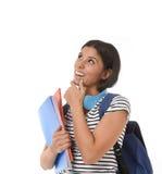 Muchacha latina hermosa y de moda joven del estudiante que lleva a cabo el pensamiento de la mochila de la carpeta y del libro de Foto de archivo libre de regalías