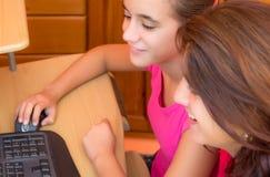 Muchacha latina joven y su madre que trabajan en un ordenador Foto de archivo libre de regalías