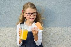 Muchacha linda 7 años que comen un bocadillo y que beben el zumo de naranja fotos de archivo libres de regalías
