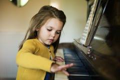 Muchacha linda adorable que juega concepto del piano Imagen de archivo