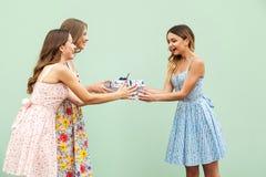Muchacha linda adulta joven que da el regalo de la sorpresa al amigo bonito de los hes Fotografía de archivo