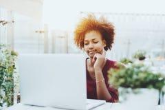 Muchacha linda afroamericana con el ordenador portátil en café al aire libre Fotos de archivo