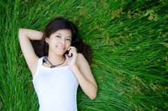 Muchacha linda asiática que miente en prado Fotografía de archivo