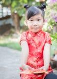 Muchacha linda con el bolsillo rojo por Año Nuevo chino Foto de archivo