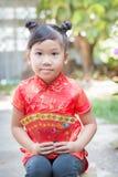 Muchacha linda con el bolsillo rojo por Año Nuevo chino Fotografía de archivo libre de regalías