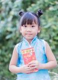 Muchacha linda con el bolsillo rojo por Año Nuevo chino Fotos de archivo libres de regalías