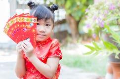 Muchacha linda con el bolsillo rojo por Año Nuevo chino Imagen de archivo libre de regalías